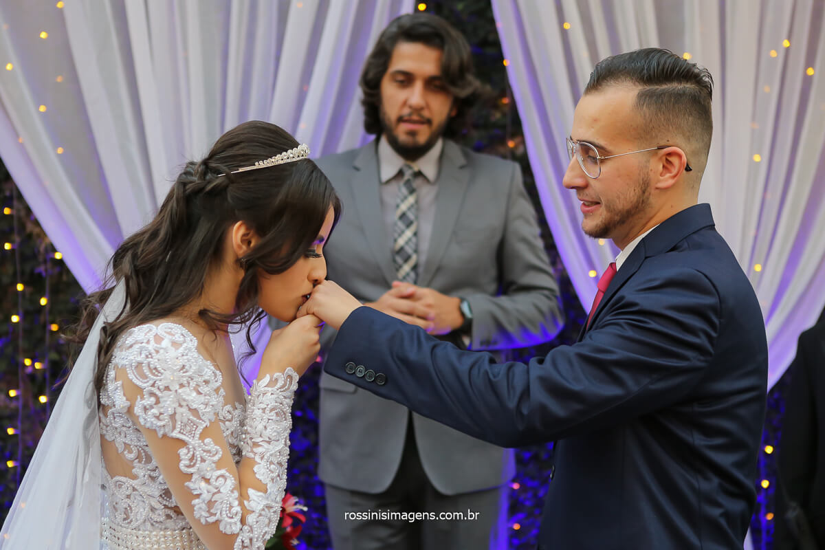 noiva coloca aliança na mão esquerda do noivo e beija a aliança na sequencia, fotografo de casamento @RossinisImagens