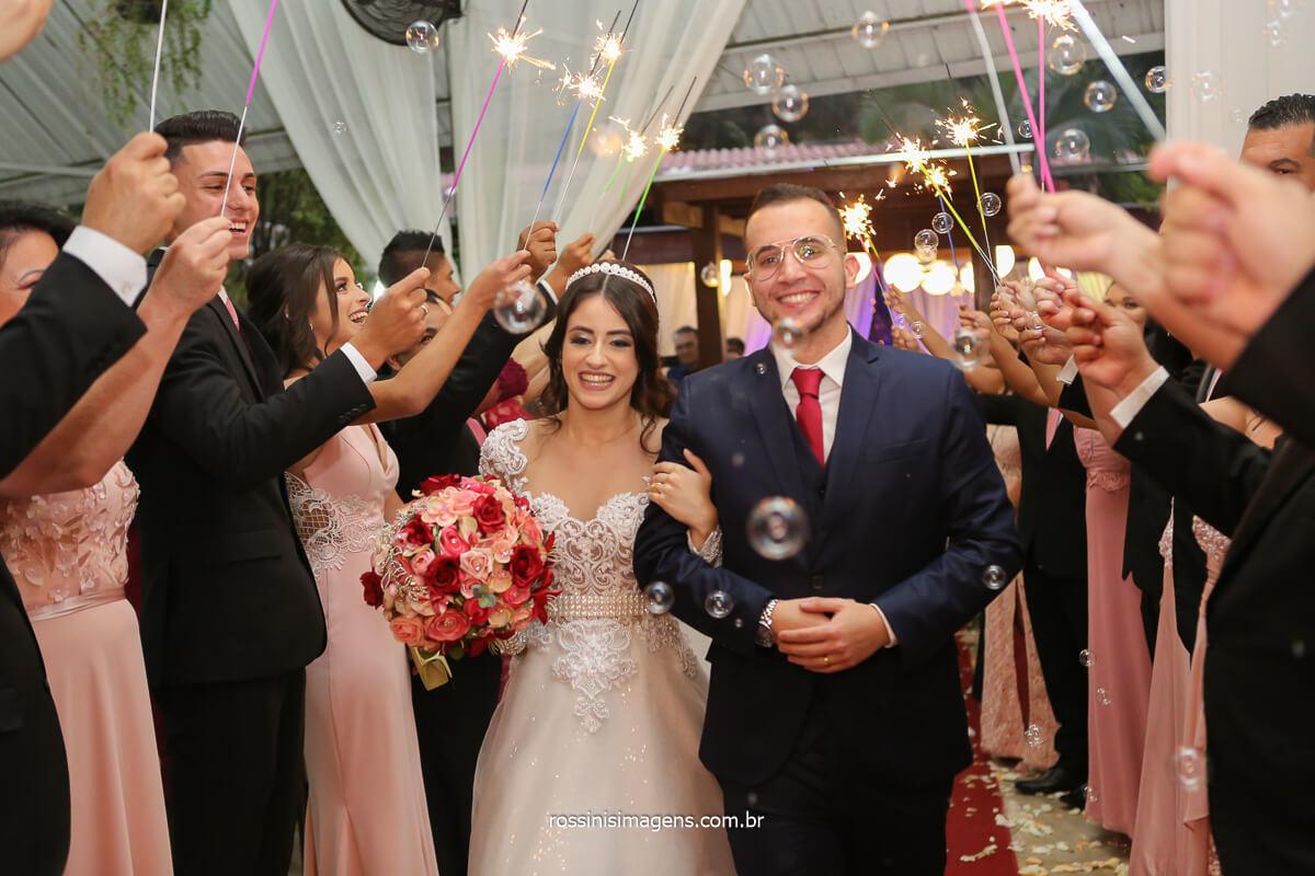 saída dos noivos Larissa e Filipe muito animada e agitada com os padrinhos com spakles e bolinha de sabão, velas sparkles, fotografo de casamento @RossinisImagens
