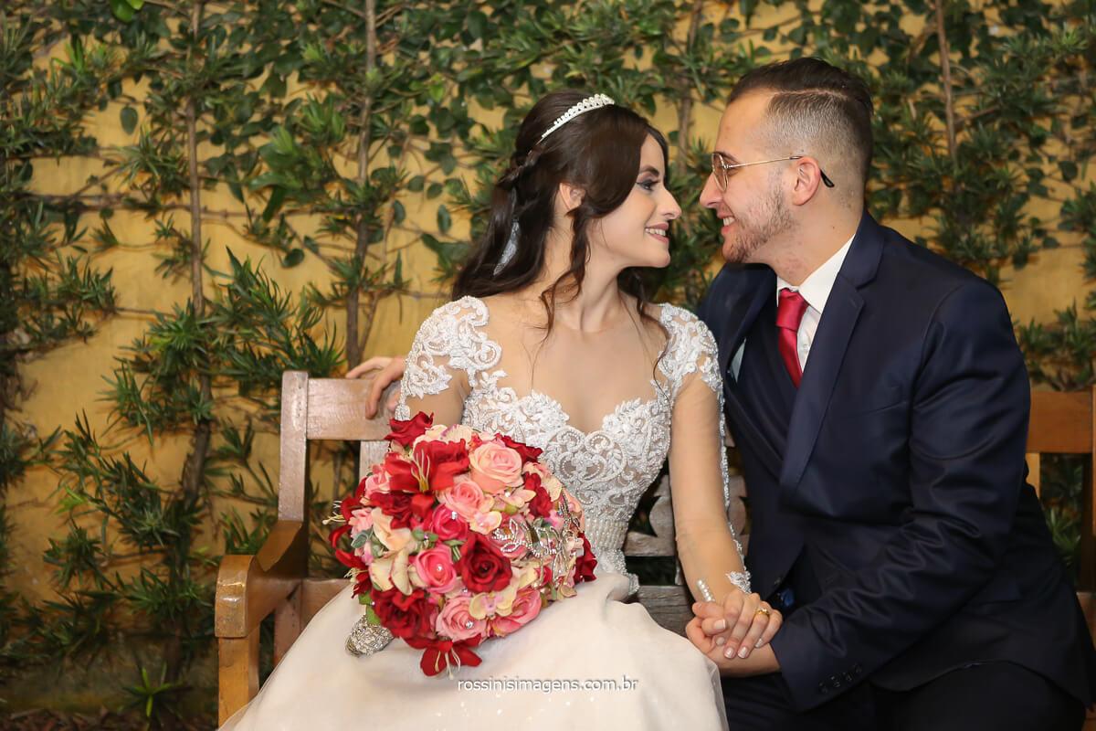 noivos sentados no banco estilo rustico de mãos dadas olhando um ao outro, fotografo de casamento @RossinisImagens