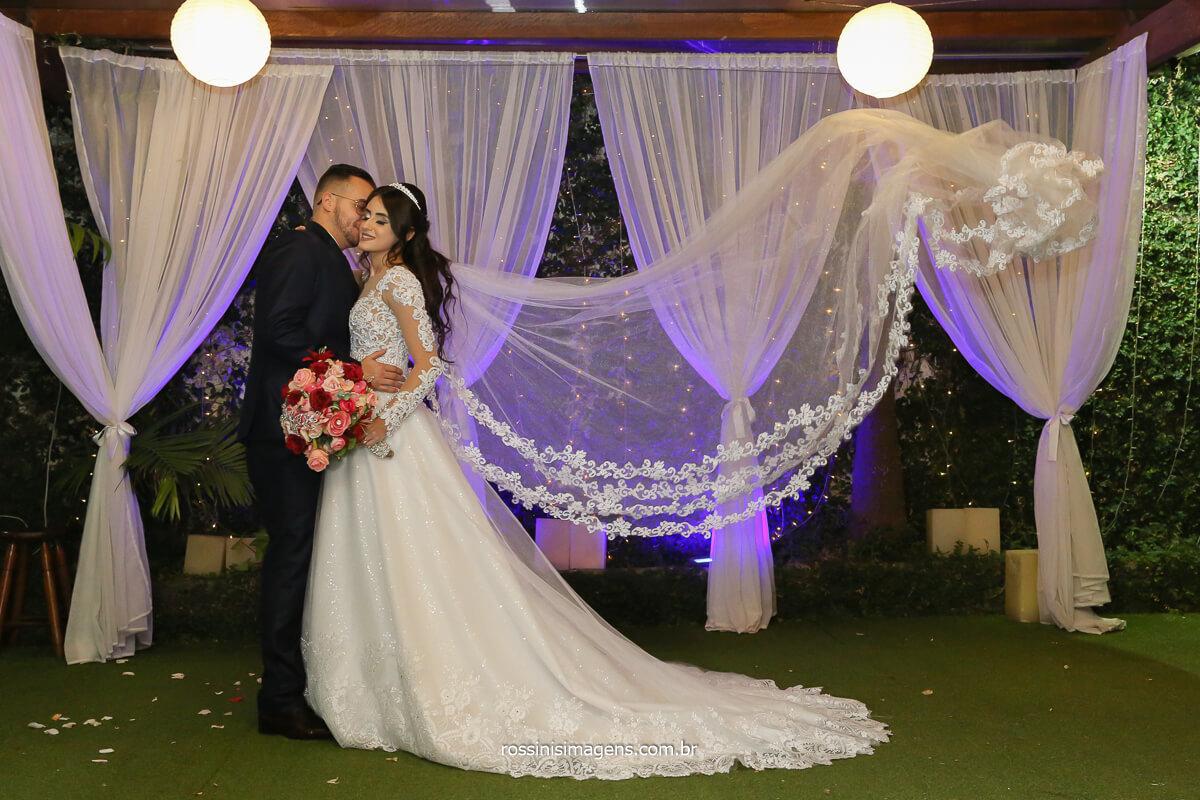 noivos em pé olhando um ao outro e o véu da noiva voando, fotografo de casamento @RossinisImagens
