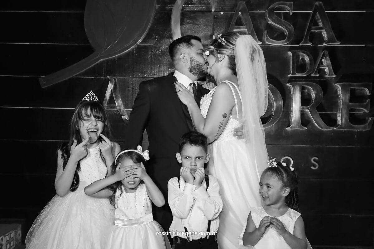 sessão de fotos com as crianças fechando os olhos e os noivos beijando, @RossinisImagens