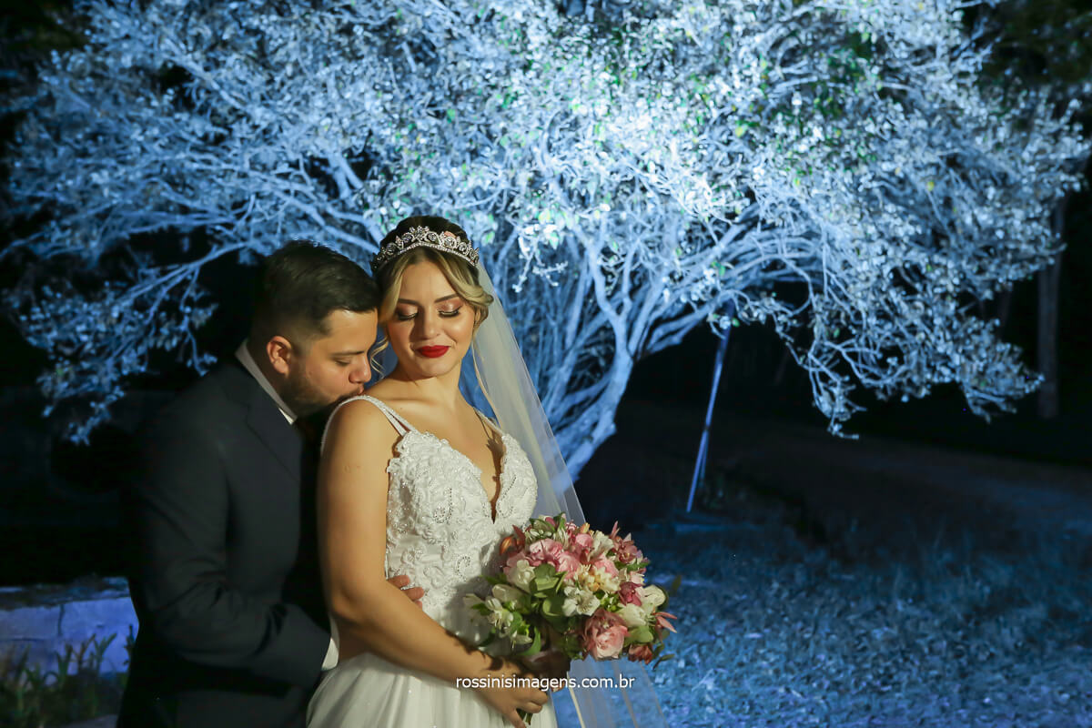 fotografia de casamento com flash externo e filtro de cor azul na arvore e casal de noivos no primeiro plano e noiva segurando o buquê, @RossinisImagens