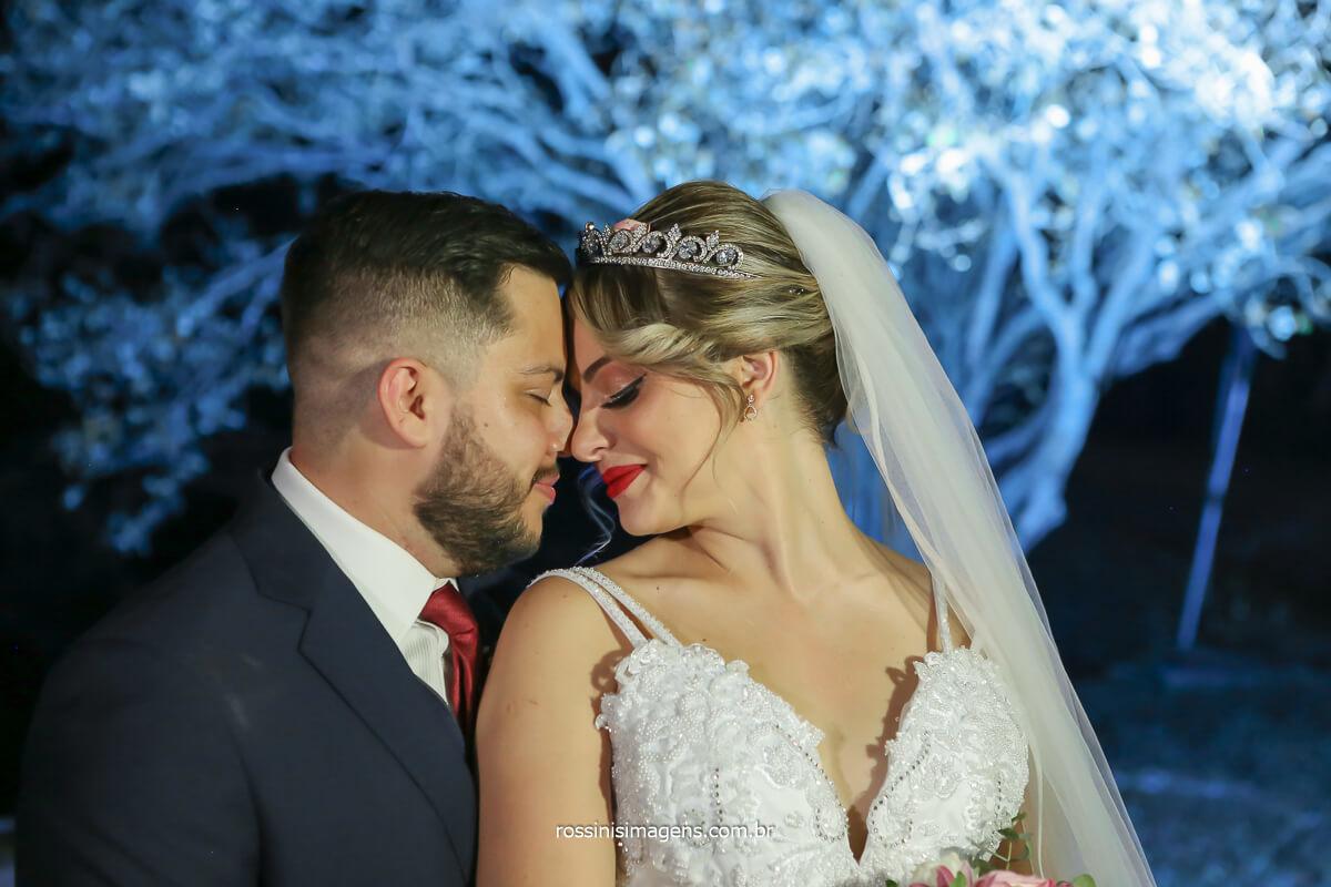 noivo de terno azul e gravata marsala abraçado com a noiva de vestido lindo branco com véu e tiara de cabelo e arvore ao fundo iluminada com flash off câmera, fotografia profissional de casamento em mogi das cruzes, @RossinisImagens