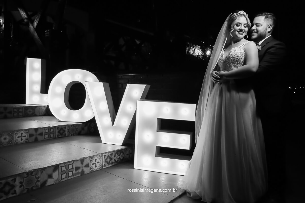 fotografia profissional de casamento em mogi das cruzes, casamento na casa da arvore, noivos em frente ao letreiro love luminoso em fotografia preto e branco realçando os detalhes e composição, @RossinisImagens