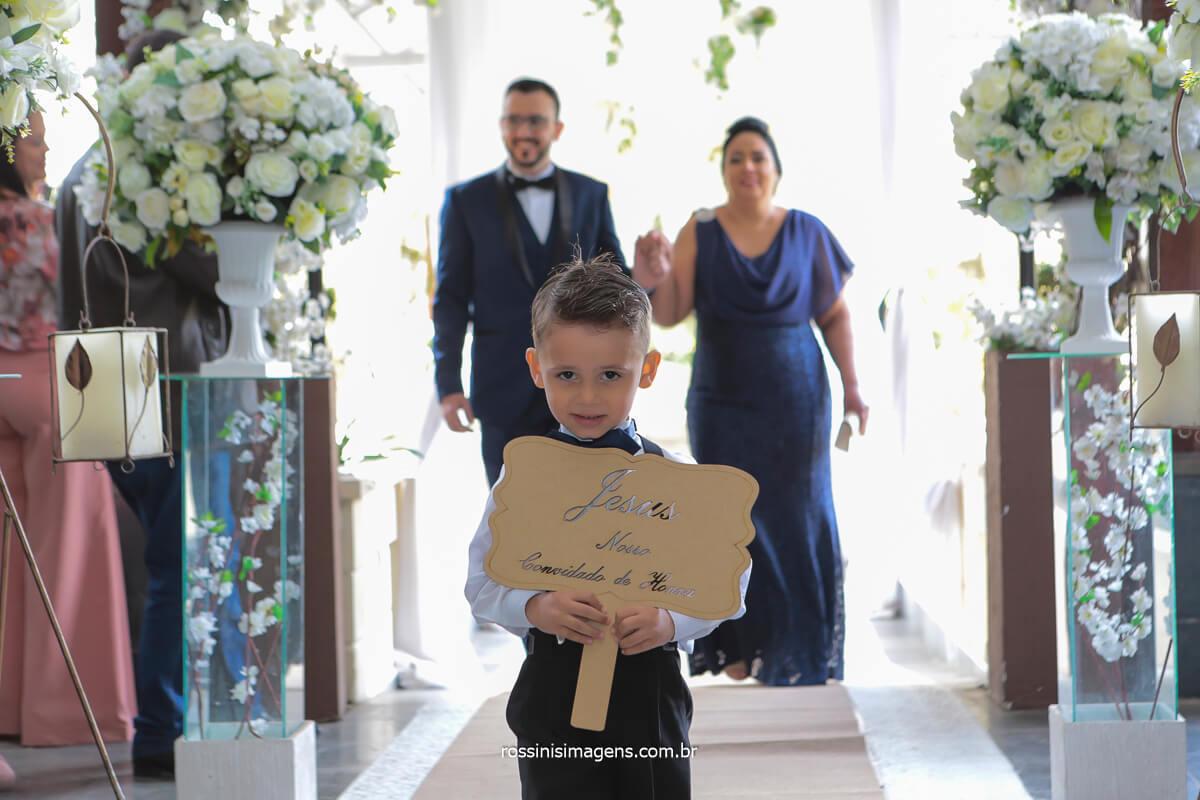 entrada do noivo com a sogra mãe da noiva e a plaquinha de jesus convidado de honra com a criança que vem a frente deles, @RossinisImagens