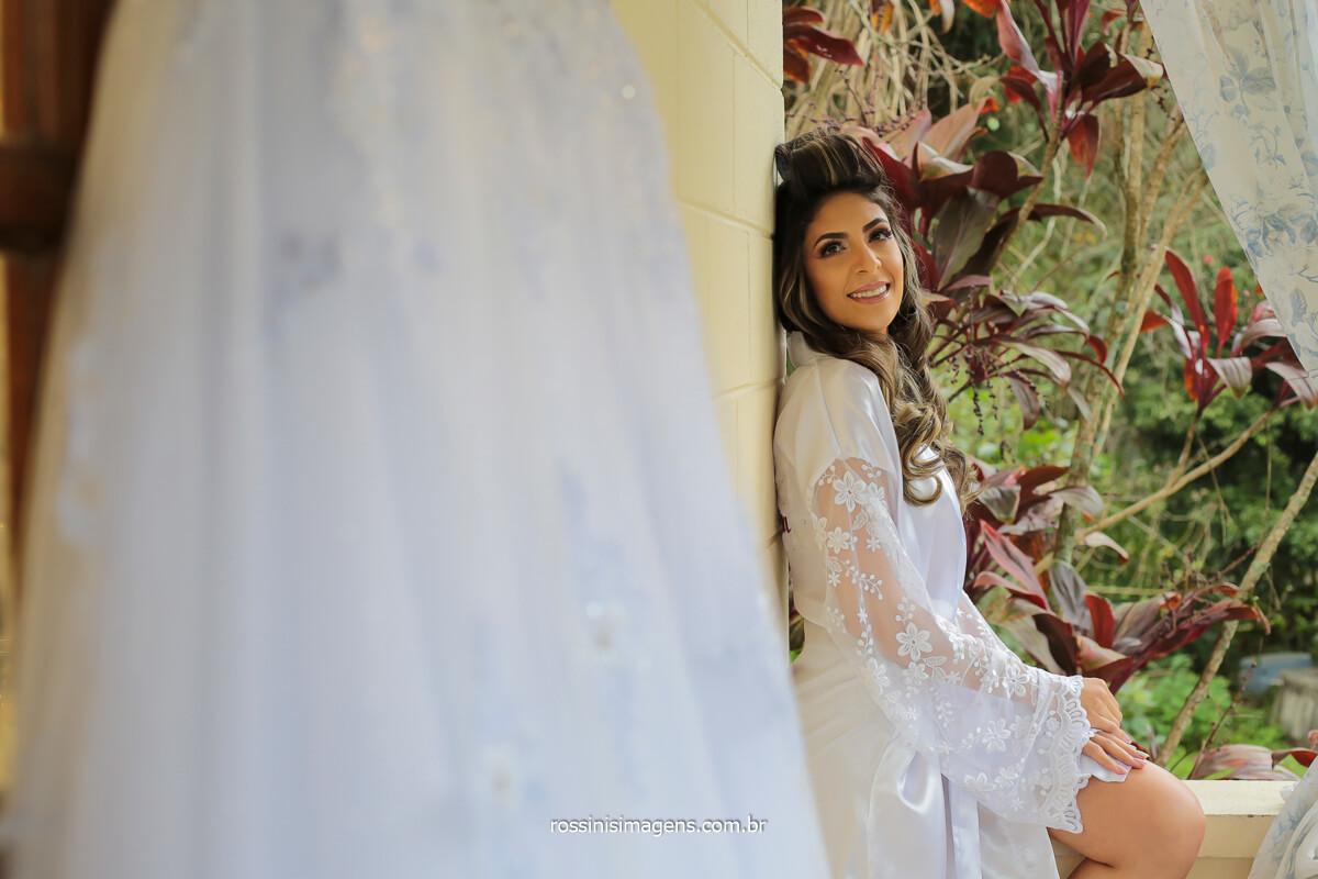 noiva de robe na varanda da sala admirando o vestido branco, @RossinisImagens