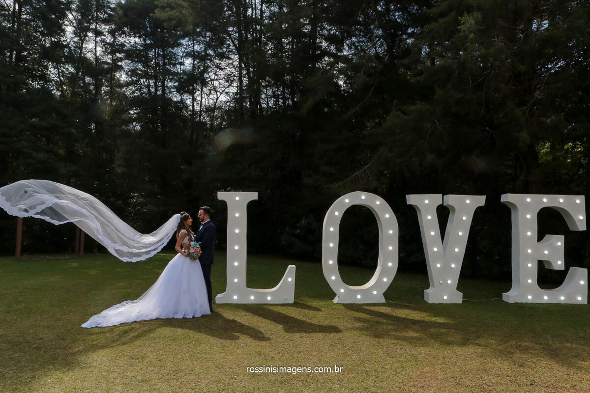 fotografo de casamento em são paulo no espaço balboa na serra da cantareira em sp, noivos enfrente ao letreiro love e o véu da noiva voando, @RossinisImagens
