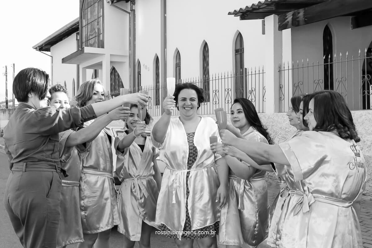 dia da noiva ao lado da igreja em poa na vila varela, madrinhas brindando com a noiva em frente a igreja antes do casamento, @RossinisImagens
