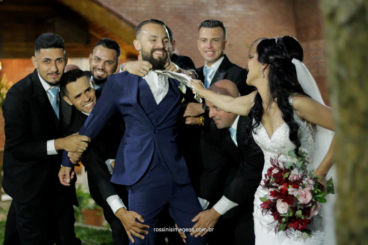 fotografia dos padrinhos com a noiva puxando o noivo pela gravata, momento descontraído, @RossinisImagens