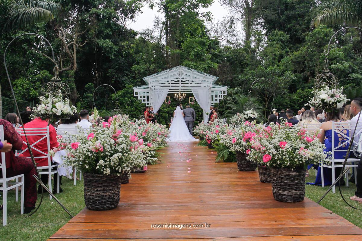 fotografia de decoração do altar com os noivos durante a cerimonia de casamento em poá, casamento diurno ao ar livre