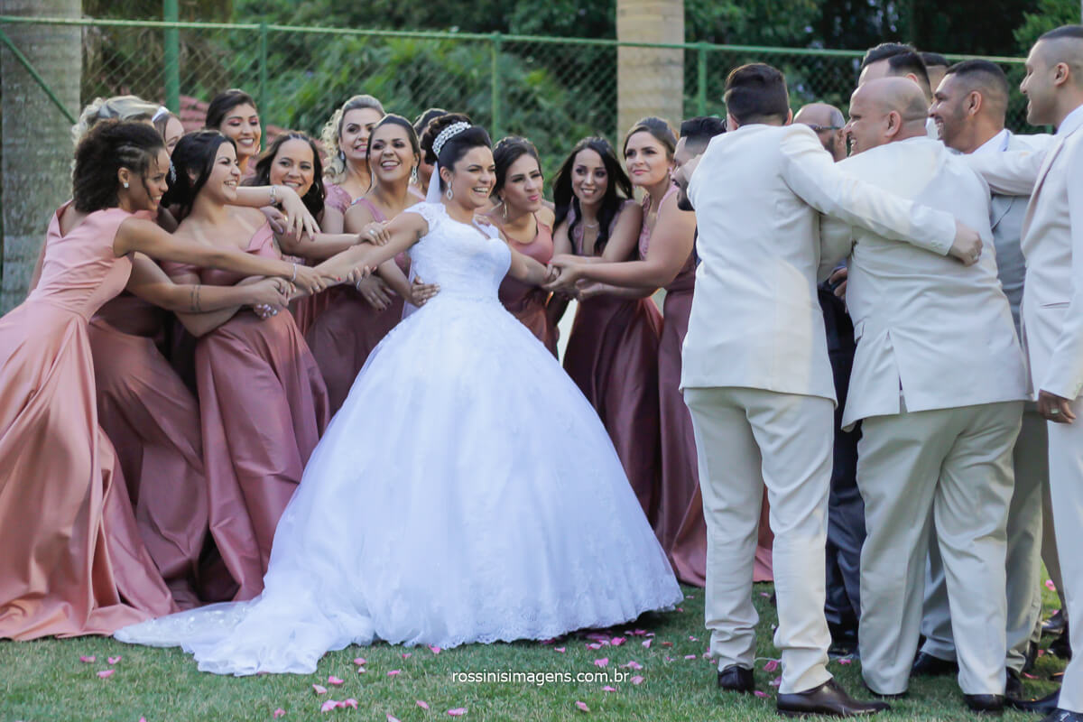 madrinhas puxando a noiva e os padrinhos puxando o noivo, sessão de fotos coletivas co o padrinhos