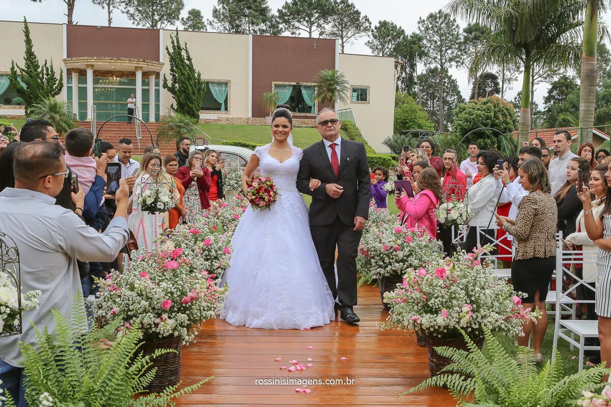 fotografia da entrada da noiva com seu pai e o o lindo buquê de flores