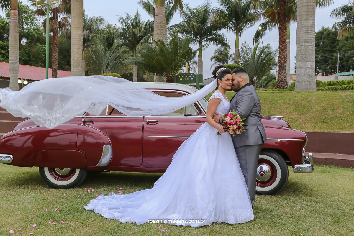 fotografia do casal juntos com o véu voando, wedding day, ao ar livre