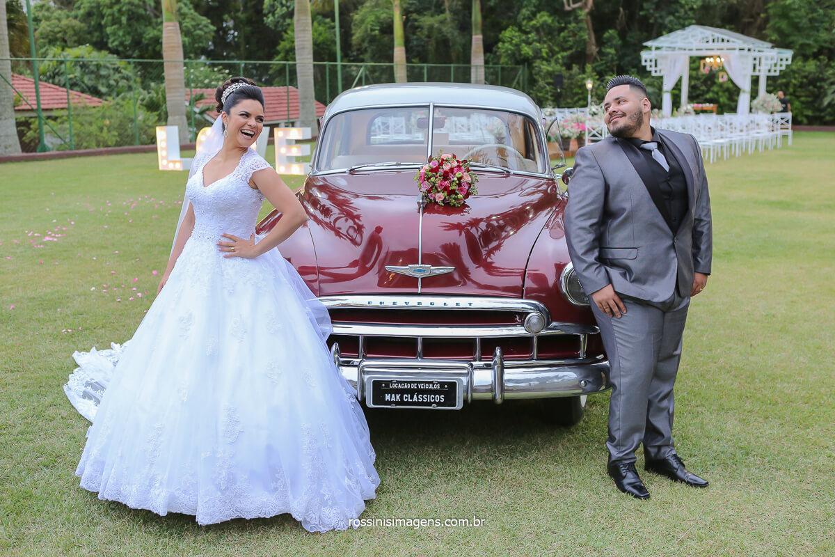 noivos a frente do carro clássico para a sessão de fotos do registro fotográfico do casamento