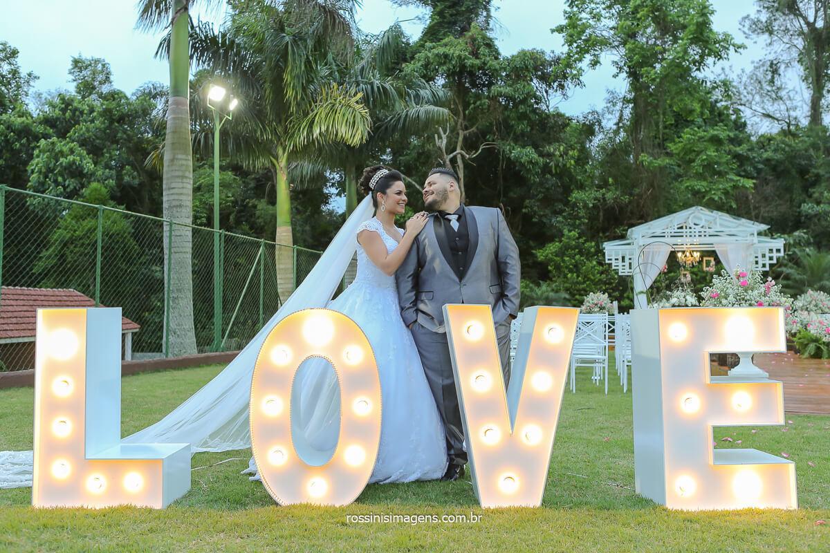 fotografia do casal no letreiro love branco casamento ao ar livre de dia fotografia de casamento em poá