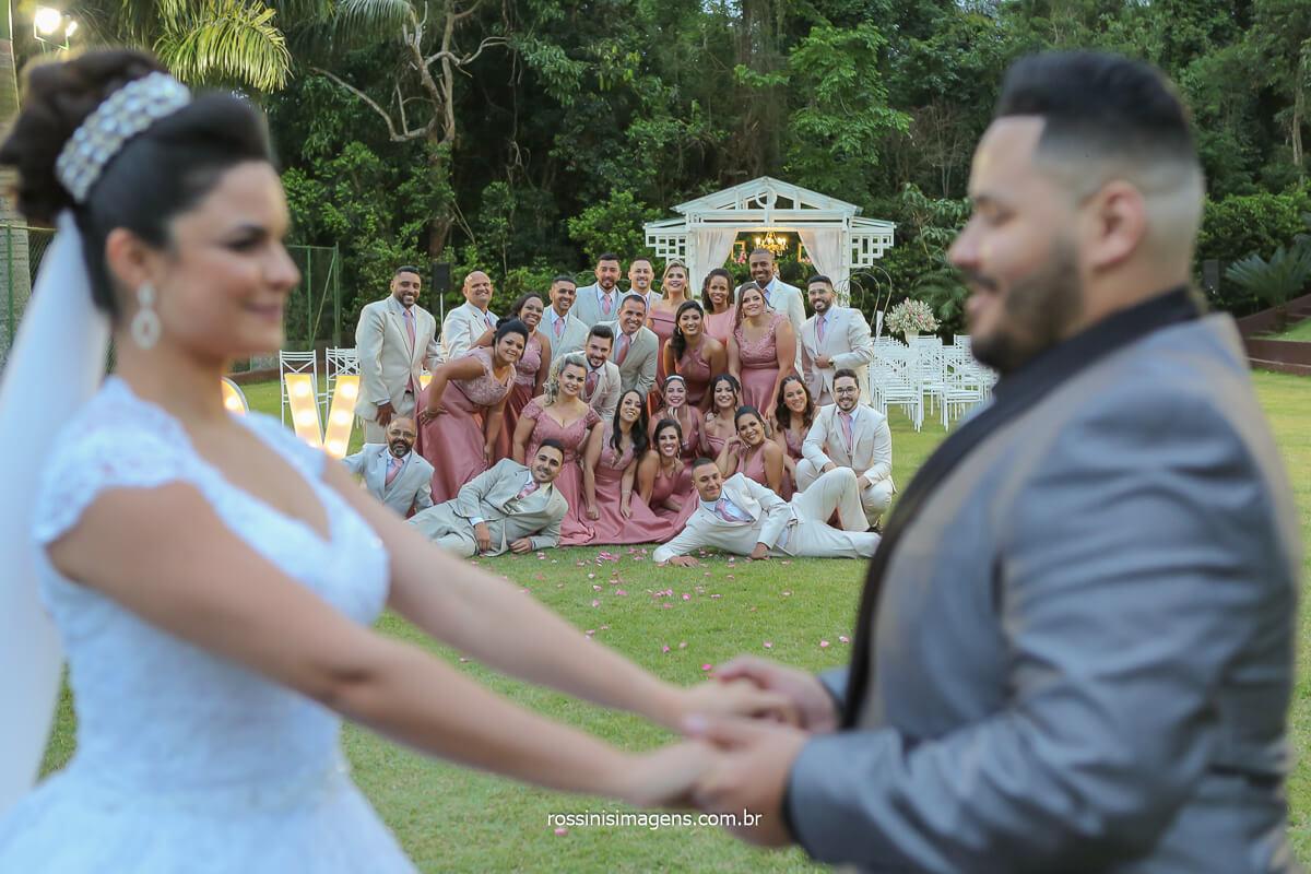 fotografia coletiva com os padrinhos e madrinhas juntos e misturados e o casal a frente segurando as mãos