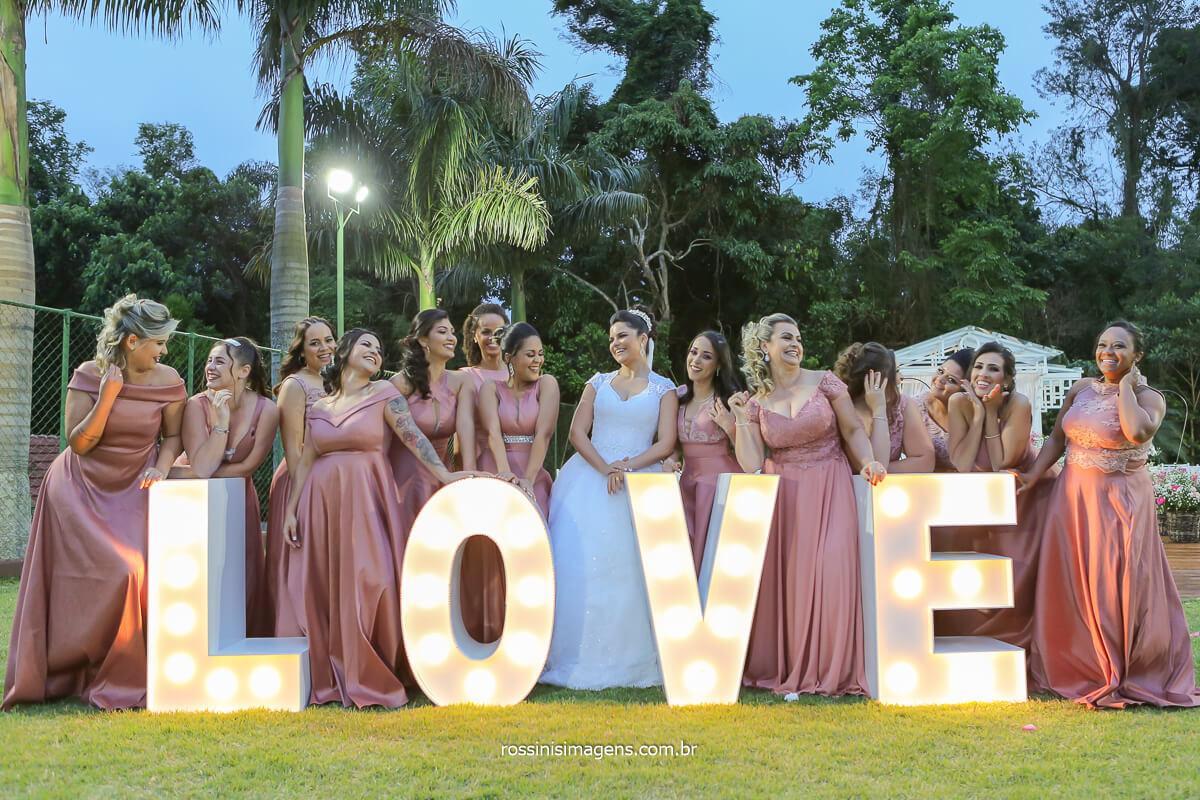 fotografia da noiva com as madrinhas no letreio love na chácara Torres casamento de dia ao ar livre