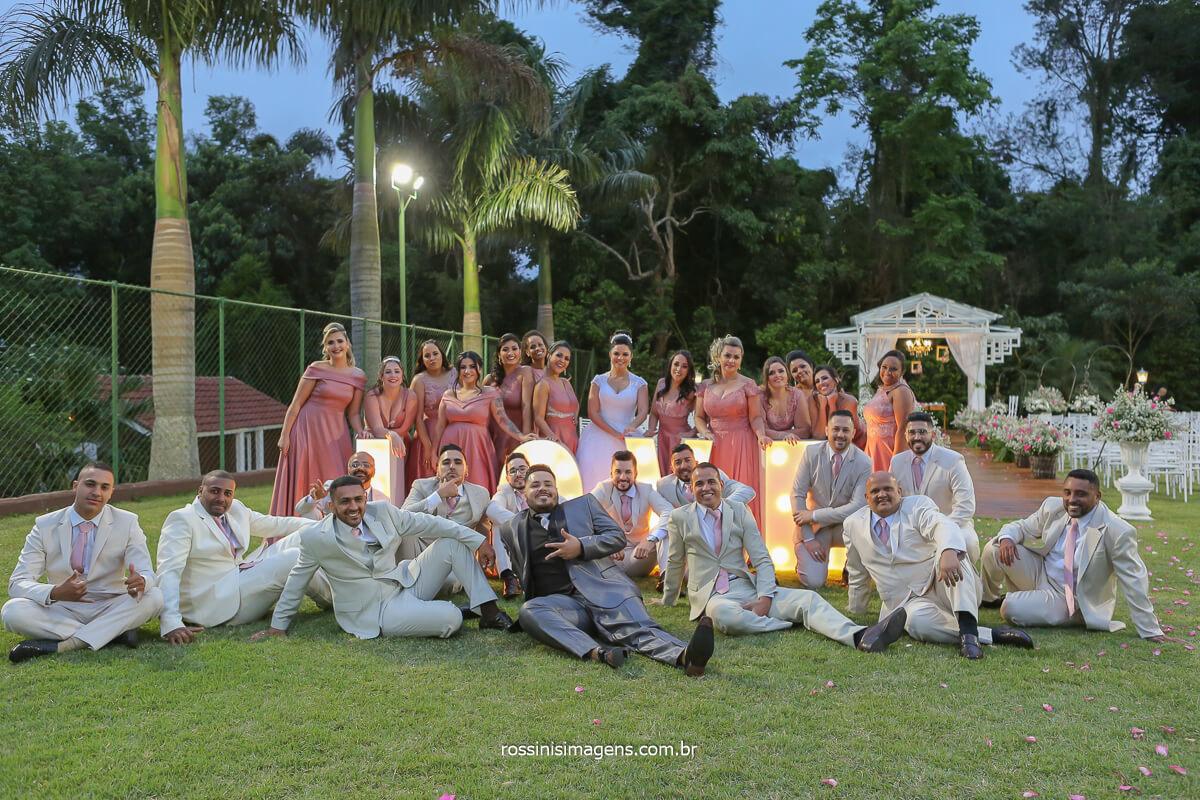 fotografia dos noivos com os padrinhos e madrinhas no chão