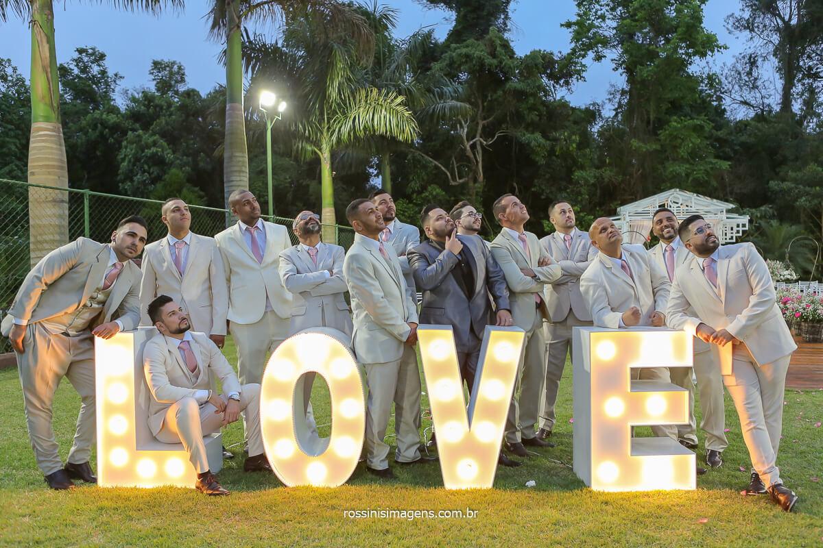 fotografia do noivo com os padrinhos o letreiro love casamento de dia ao ar livre