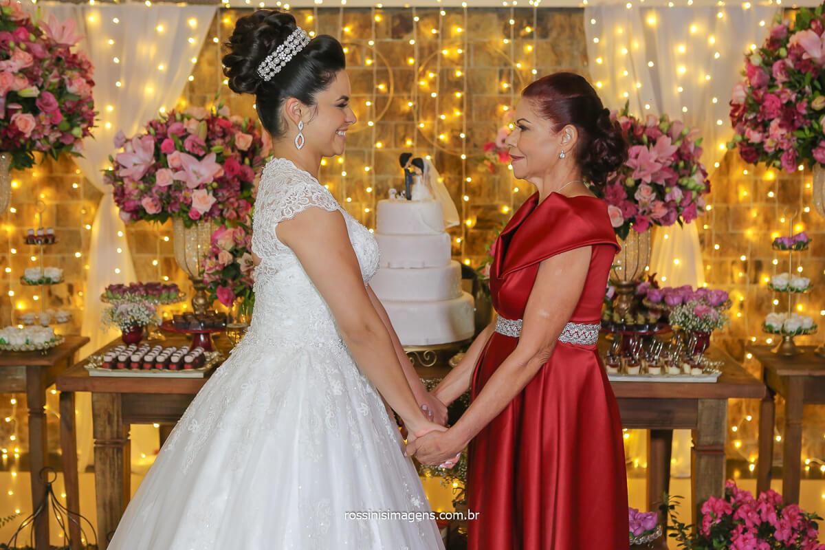 fotografia da noiva com a mãe na mesa do bolo, dia do casamento casal mesa do bolo