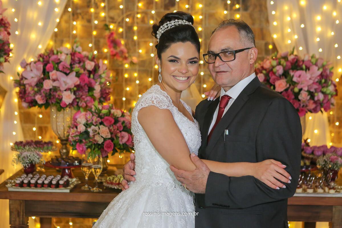 fotografia do casamento noiva com seu pai na mesa do bolo