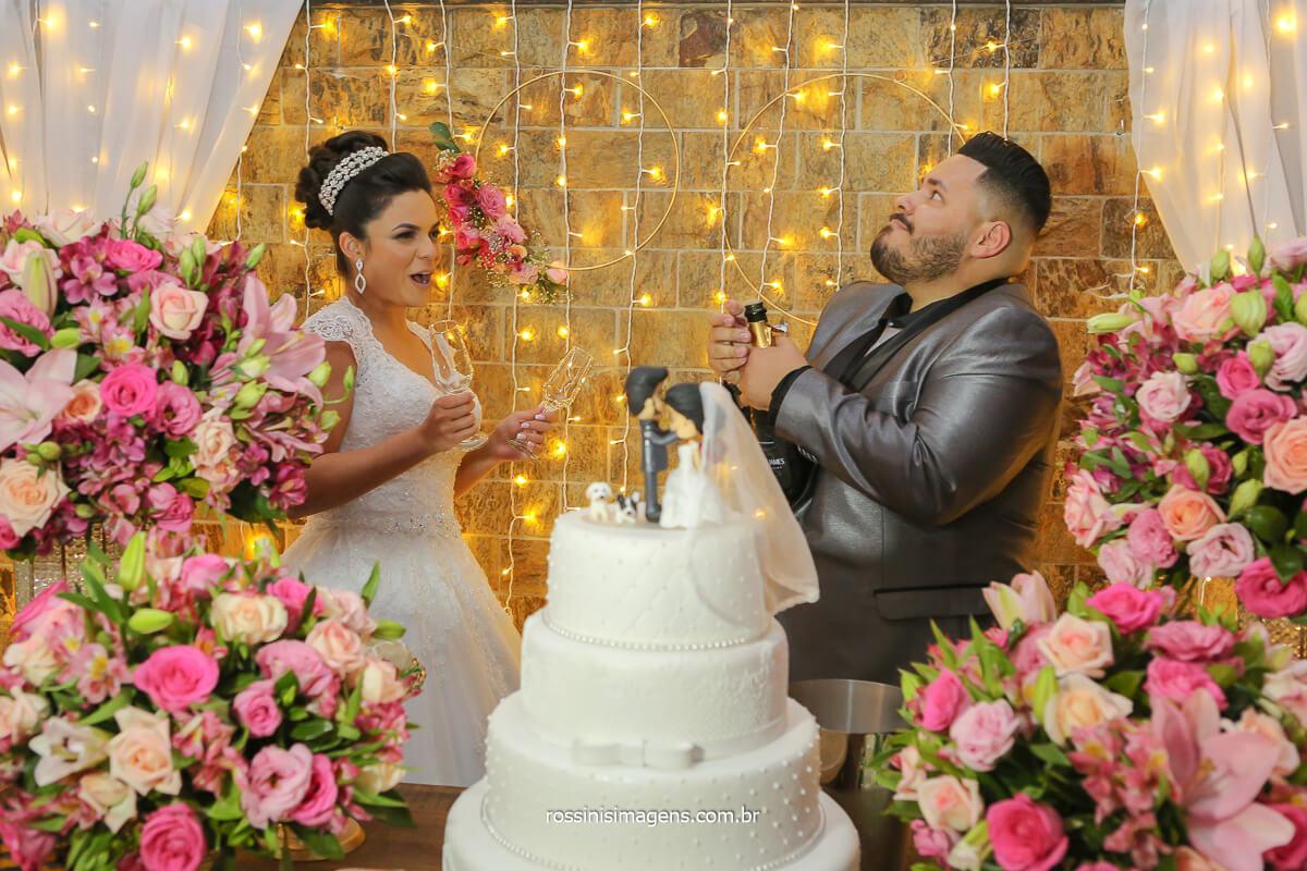fotografia noivo abrindo champanhe na mesa do bolo