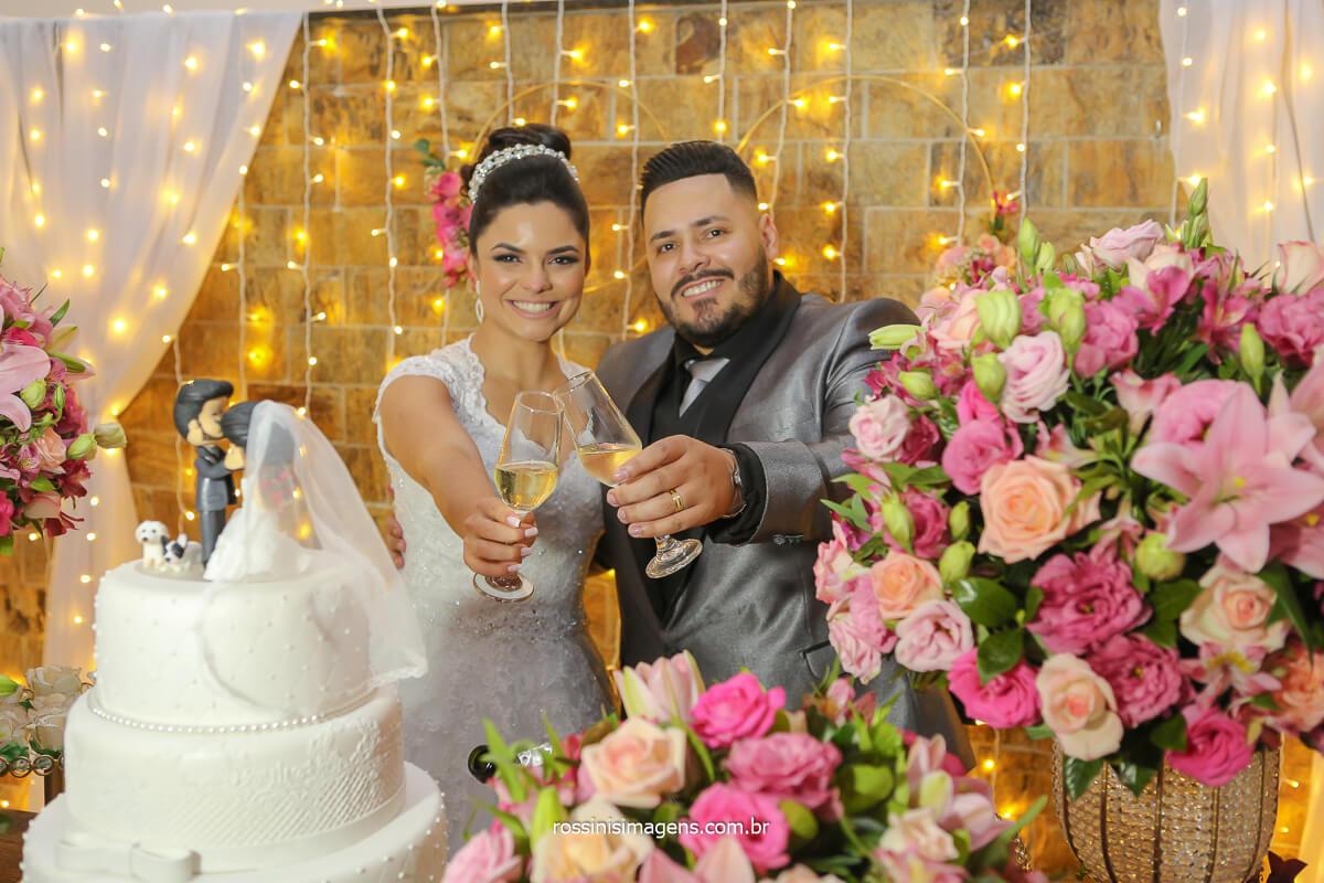 fotografia do casal brindando na mesa do bolo decoração com flores naturais e cortina de led para climatizar o romance do casal