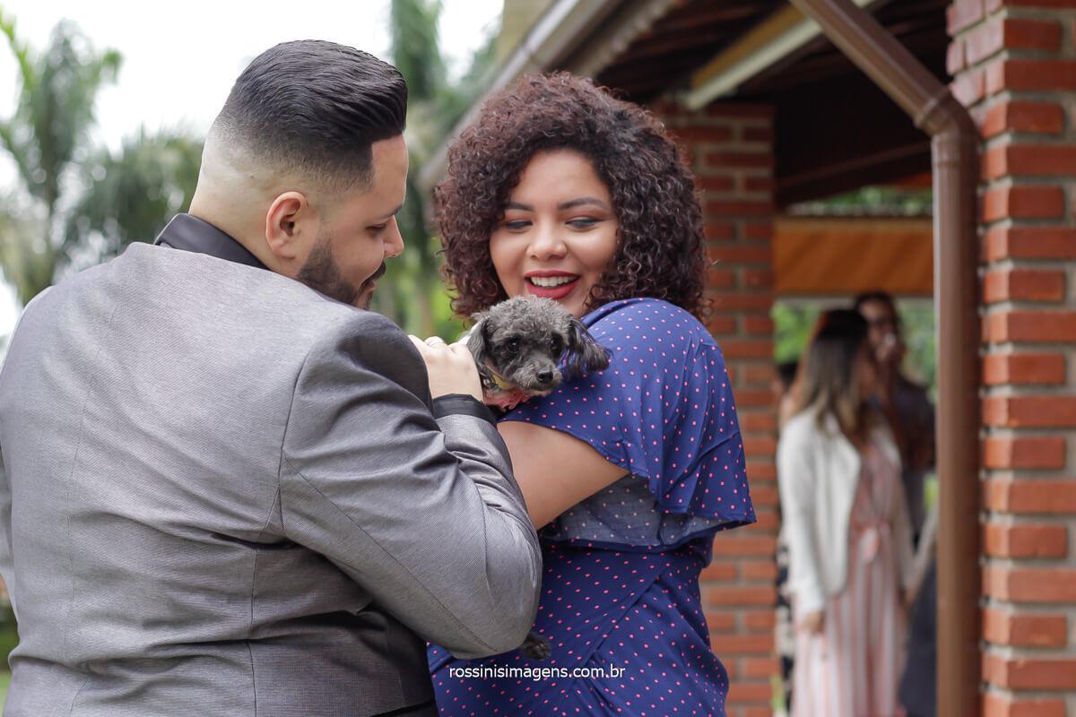 fotografia do casamento noivo cumprimentando uma convidada com pet