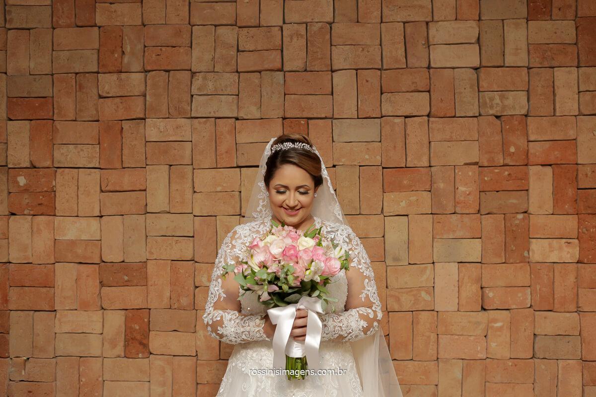 noiva com o buquê enfrente a parede rustica de tijolinho um luxo e uma oportunidade que as noivas pouco tem, @RossinisImagens