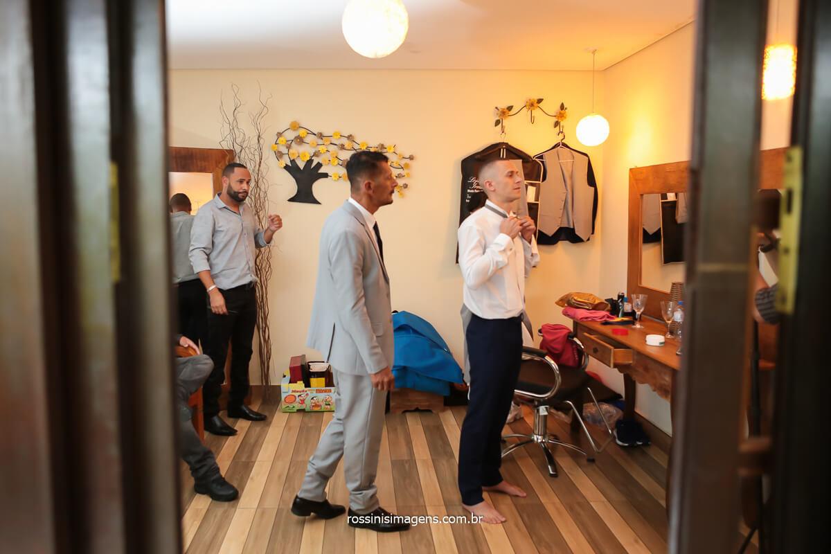 fotografia do making of dia do noivo, noivo colocando a gravata com os padrinhos e seu pai, assessoria da Tamy Ribeiro no Espaço Vista Verde e Fotografia @RossinisImagens
