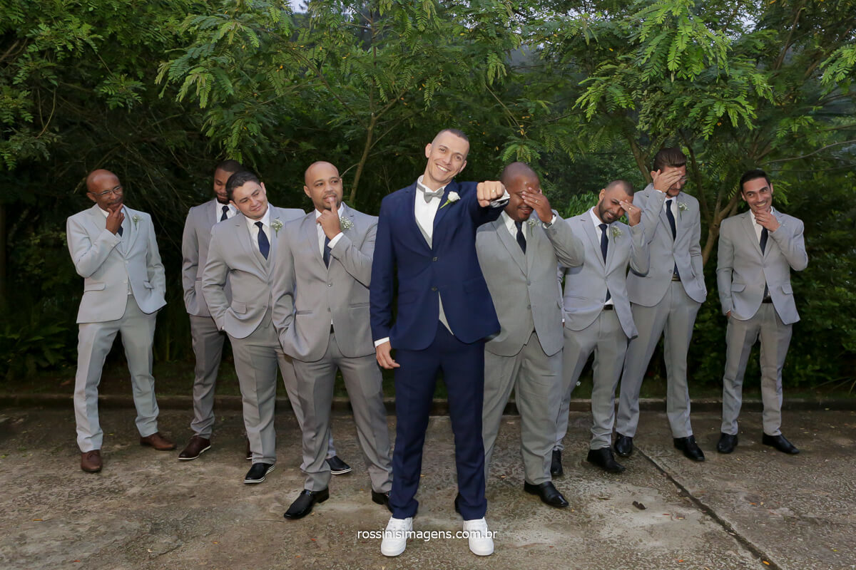 fotografia do noivo mostrando a aliança de ouro e os padrinhos ao fundo com careta, @RossinisImagens