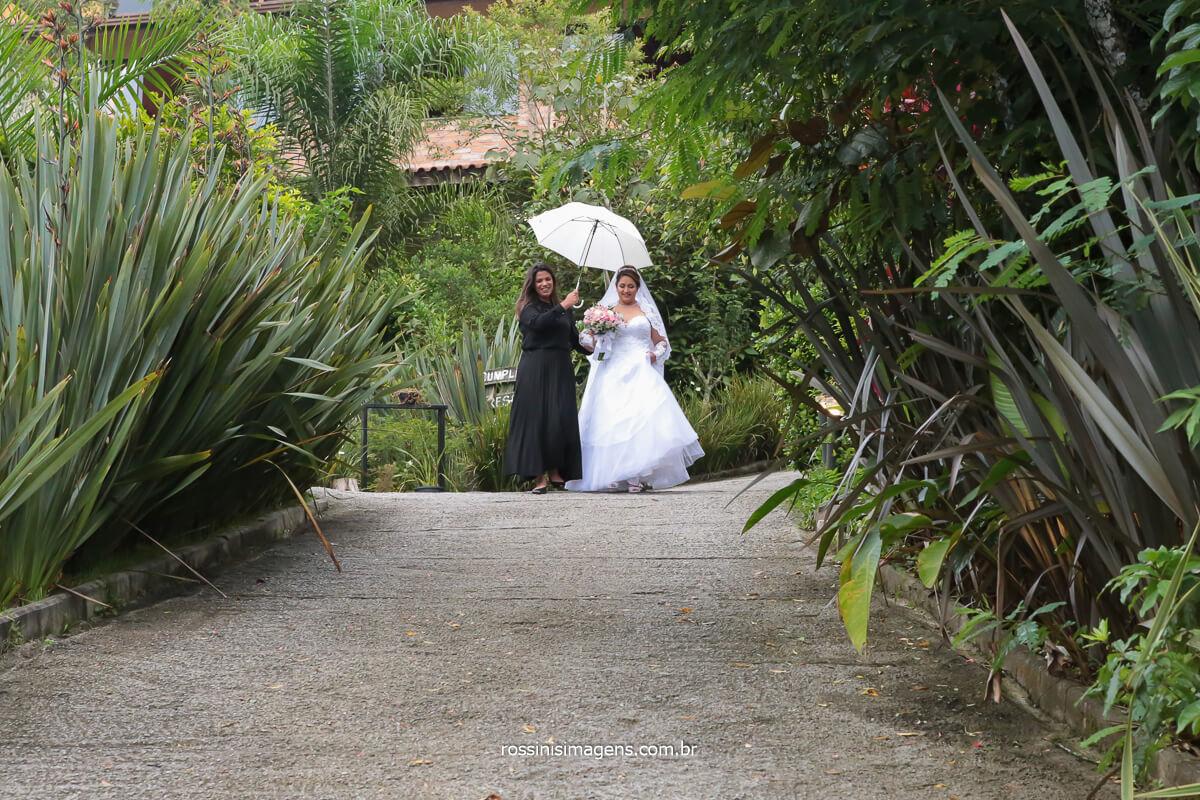 assessora chegando com a noiva para o espaço da cerimonia de casamento, dia nublado espaço vista verde, noiva chegando