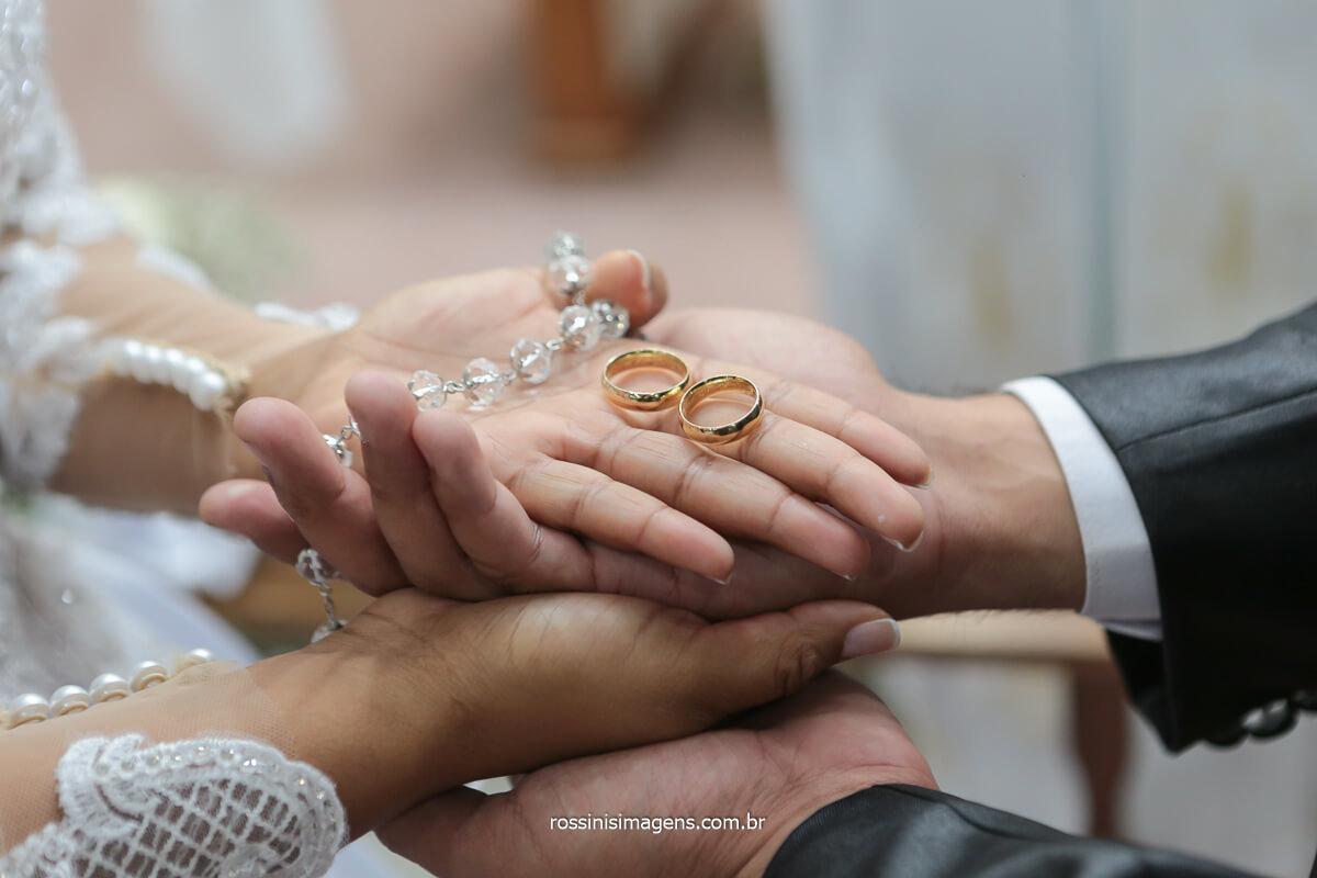 fotografia das alianças nas mãos dos noivos, no altar, @RossinisImagens