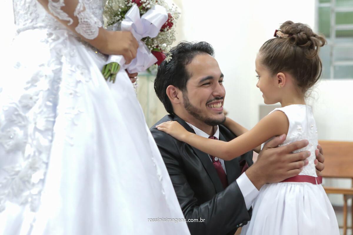 fotografia de casamento noivo abraçando a daminha de honra nos comprimentos da saída do cerimonial, @RossinisImagens