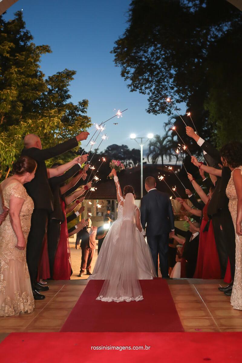fotografa de casamento registra saída dos noivo de costa evidenciando os sparkles na saída do casal, @RossinisImagens