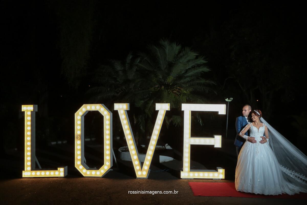 fotografo de casamento noivos Amanda e  Renato abraçados ao lado do grande letreiro Love, @RossinisImagens