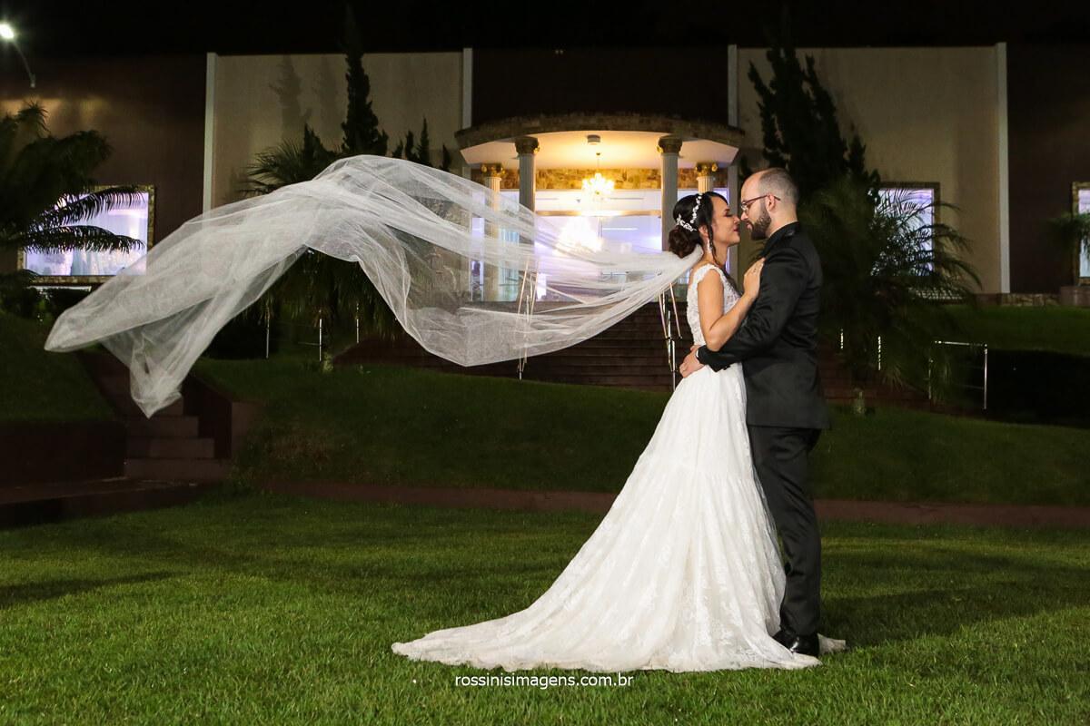 Noivo Abraçando a noiva e o Véu Voando em Frente a Chácara Torres