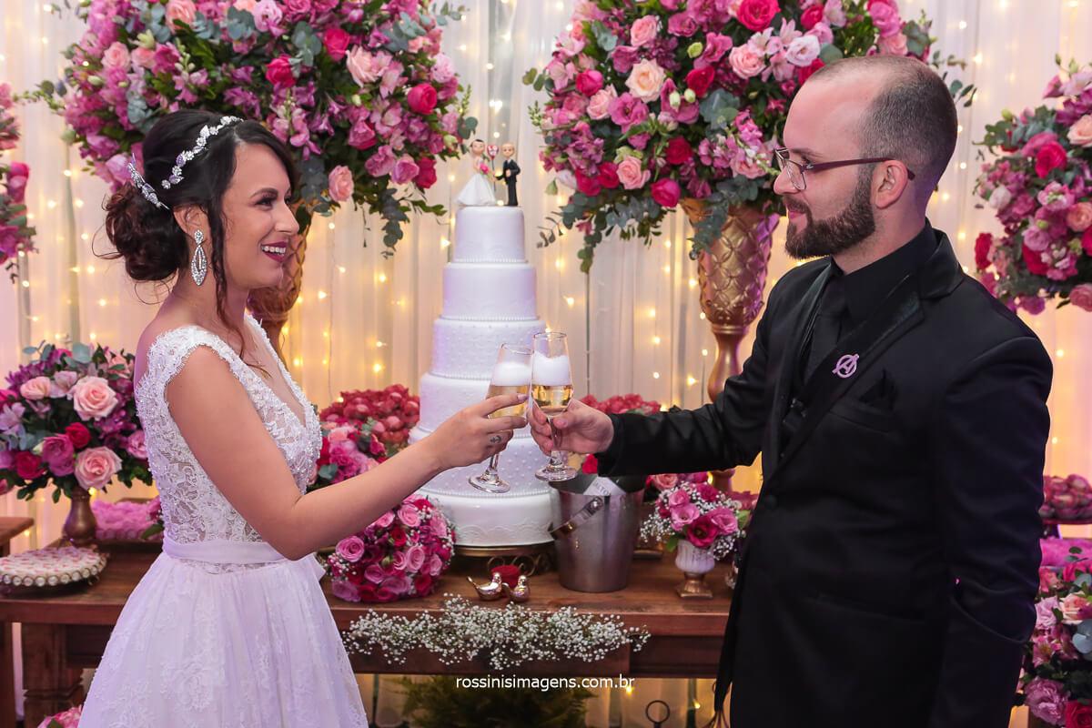 Noivos Fazem Brinde para comemorar o casamento e a chegada de sua Filha em Frente a mesa do Bolo