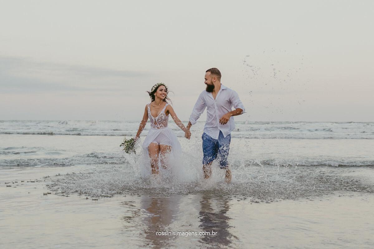 casal correndo do mar para areia, ensaio de casal na praia litoral norte