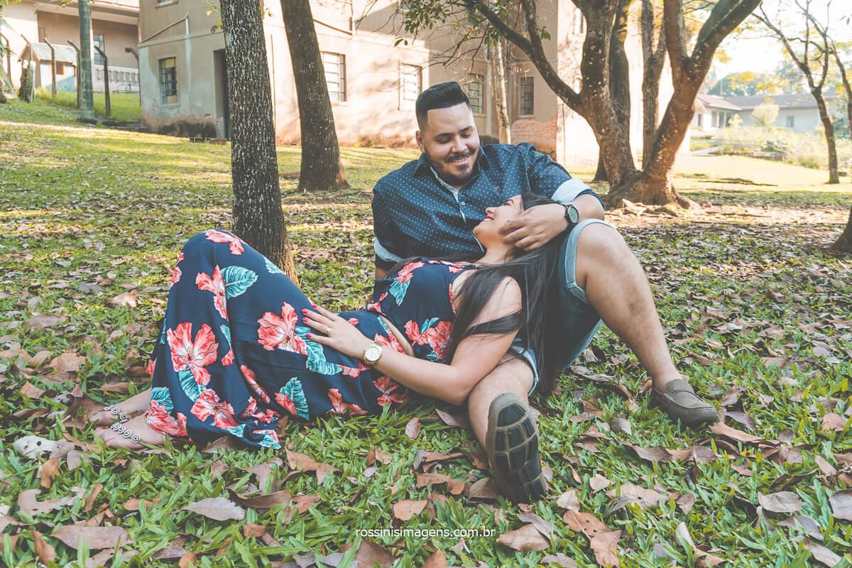 Foto do casal sentados na sombra de uma arvore, noivo fazendo carinho na noiva