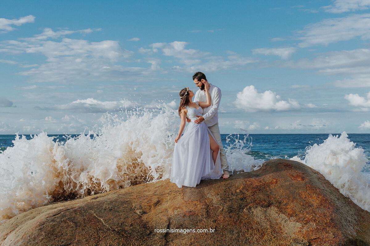 Ensaio Fotográfico de Casal de Noivos na Praia Em Cima da Pedra com Onda do Mar Batendo na Pedra, Ensaio Sensacional na Praia, Inspiração de Casais Para Ensaio na Praia