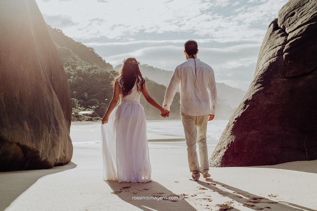 Fotografia de Casal caminhando na Beira da Praia de Mãos dadas, Inspiração de Ensaio na Praia Karol e Tiago Por Rossinis Imagens