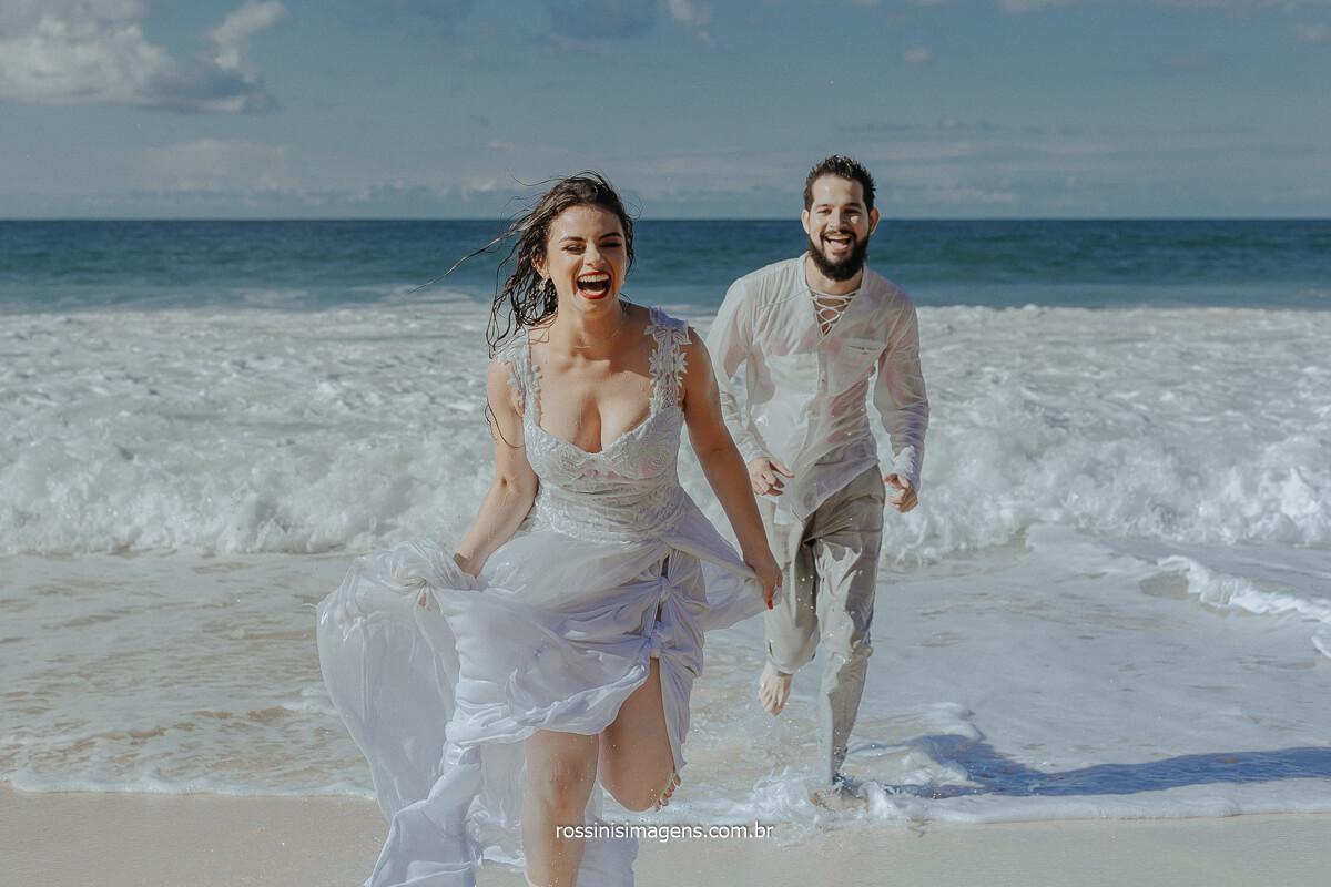 Noiva de Branco correndo do noivo Saindo do Mar Ensaio na Praia