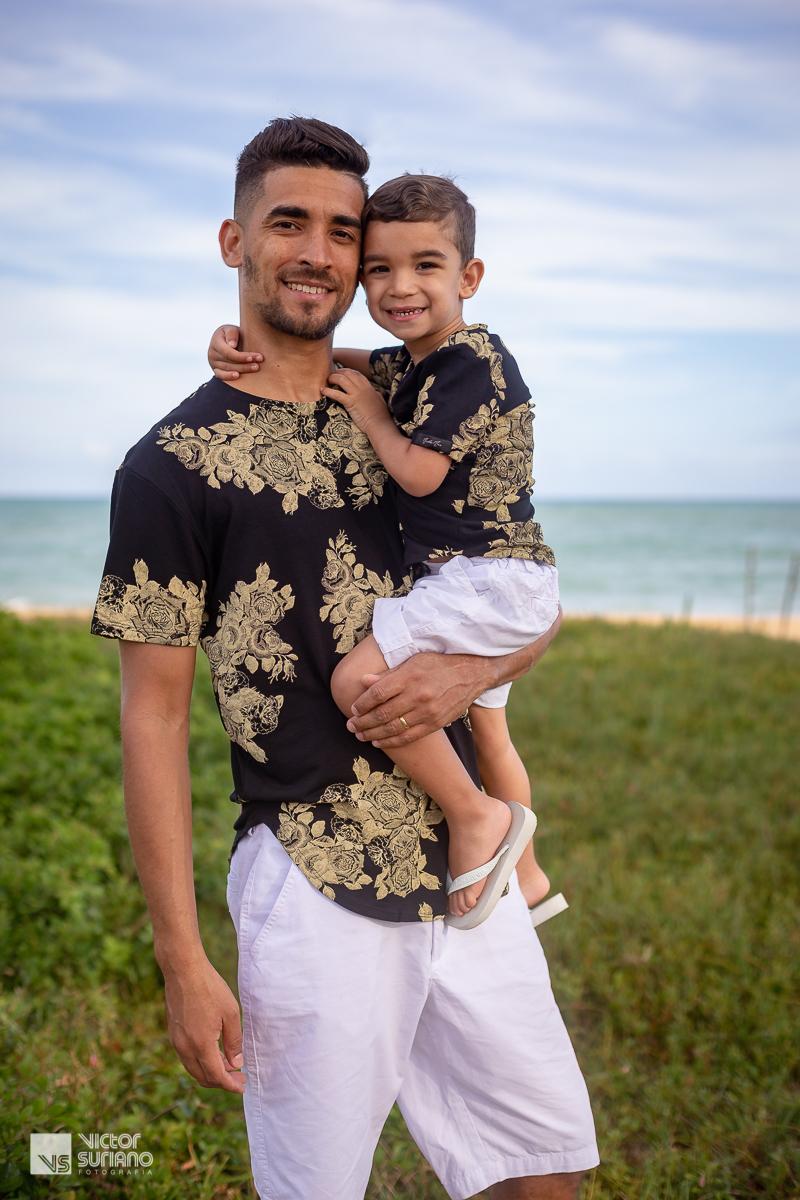 pai segurando filho no colo com camisa preta e bermuda branca