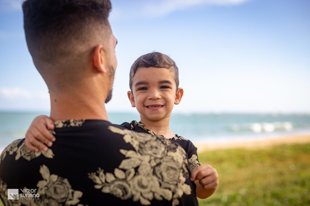 filho no colo do pai olhando para a câmera e sorrindo