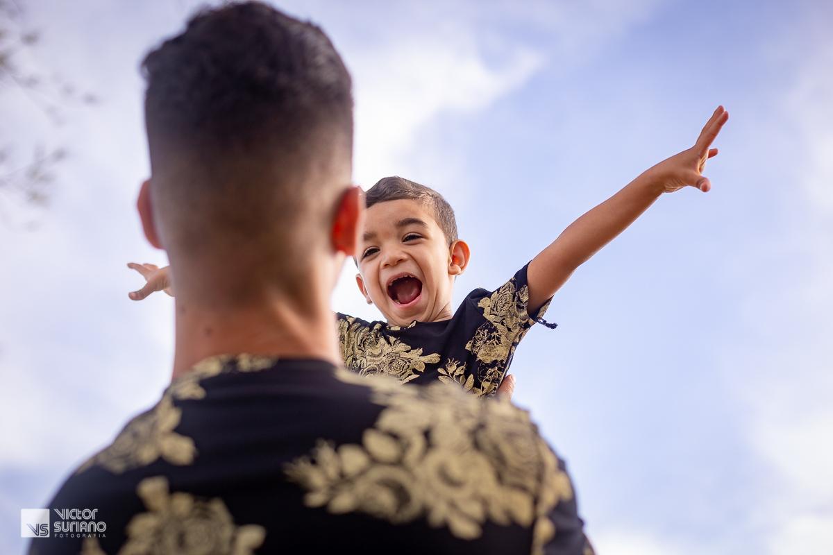 filho brincando de voar com o pai