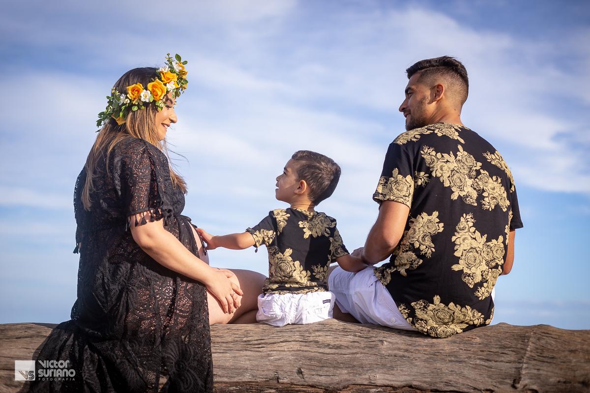 pai, mãe e filho sentado em árvore