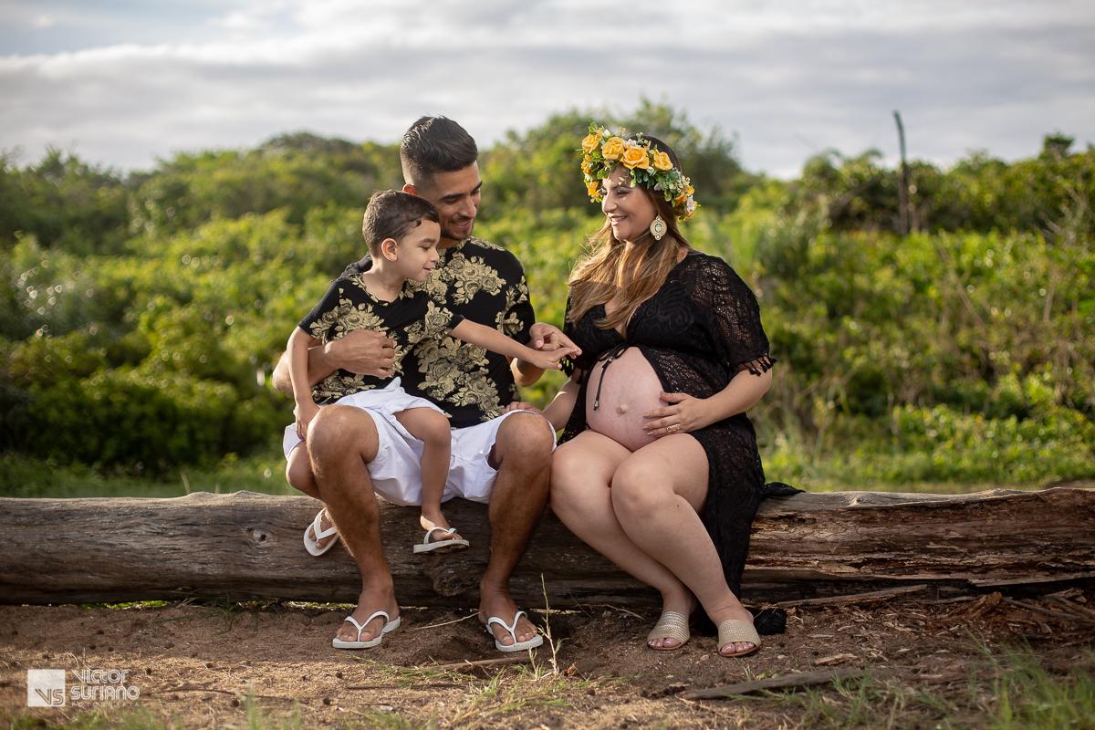 família sentada em tronco de árvore para fotos de gestante
