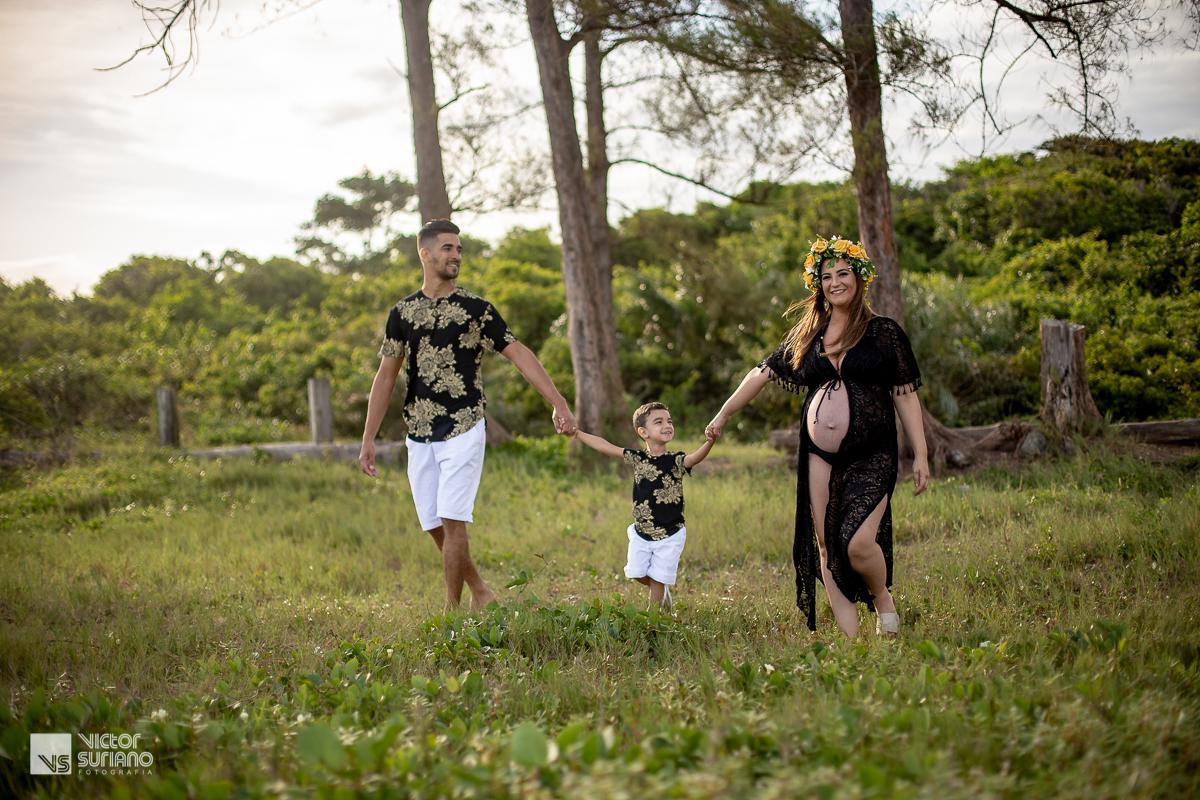família de mãos dadas e brincando na praia
