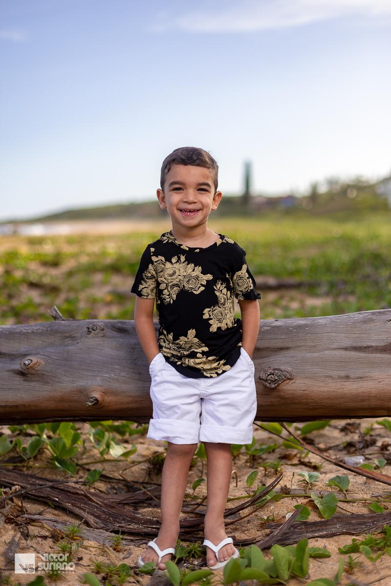 menino com as mãos no bolso e sorrindo na beira da praia